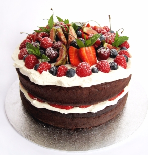 Chocolate cake covered in fresh fruit and cream